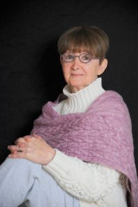 Picture of author Deanie Yasner wearing her signature round glasses with a lavender knitted wrap over a white turtleneck sweater